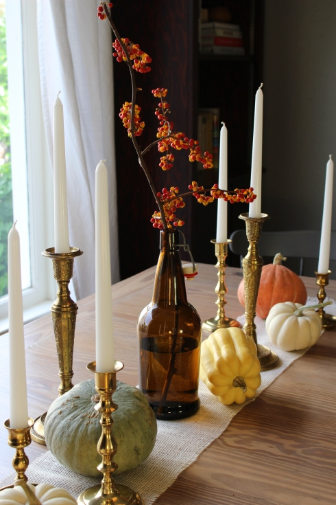 Brass candlesticks, heirloom squash and bittersweet work together as a graceful centerpiece.
