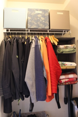 AFTER: With the chairs moved to the back of the closet, and out of season coats moved to another closet, there is now room for in-season coats and to hang guests jackets. Hanging cubbies organize the tablecloths.
